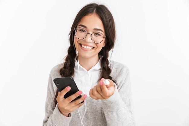 白い壁の上に孤立して立って、イヤホンで音楽を聴いて、携帯電話を持ってユニフロムを身に着けている魅力的な陽気な女子高生
