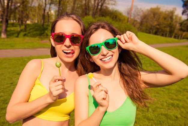 Привлекательные веселые улыбающиеся девушки, гуляющие в парке с леденцами на палочке