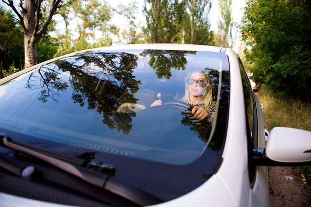 Attractive cheerful woman driver sits in the driver's seat of a modern car
