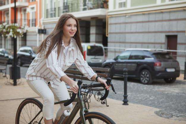 笑顔、街の通り、コピースペースで彼女の自転車に乗って魅力的な陽気な女性