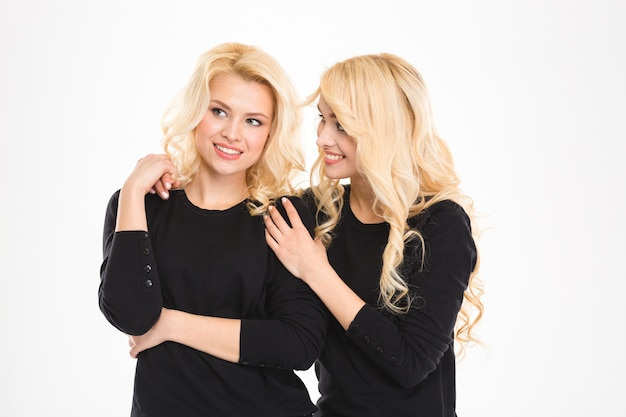 Attractive cheerful young blonde sisters twins talking and looking away