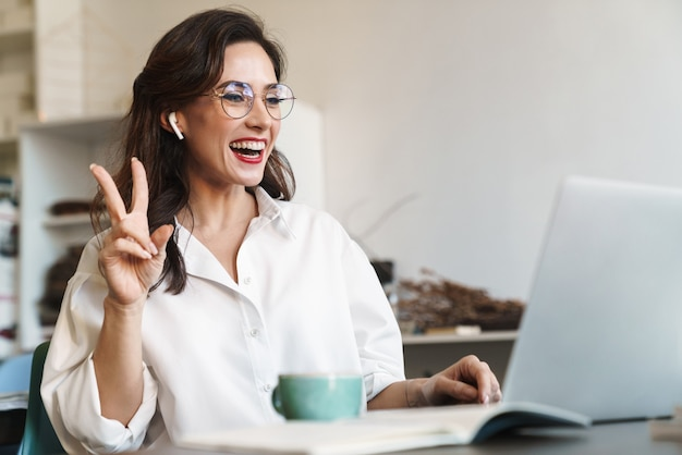 Attractive cheerful young brunette businesswoman sitting at the cafe table with laptop computer indoors, wearing wireless earphones, audio call, peace gesture
