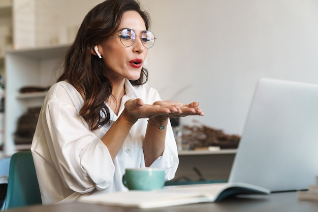 Attractive cheerful young brunette businesswoman sitting at the cafe table with laptop computer indoors, wearing wireless earphones, audio call, sending kiss