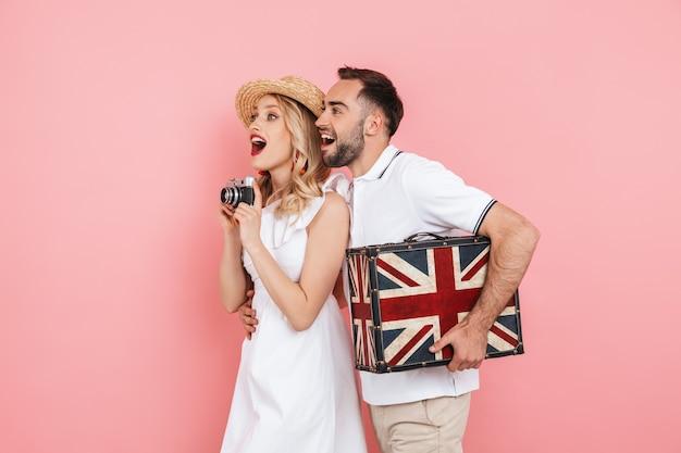 Привлекательная веселая молодая пара, стоящая вместе изолированно над розовым, путешествующая вместе, неся чемодан