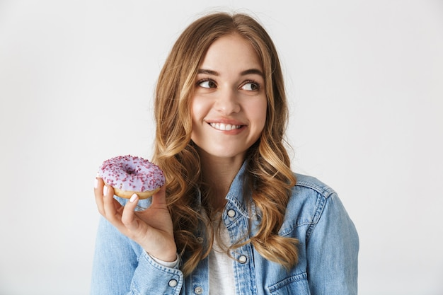 Attractive cheerful young girl standing isolated over white , holding tasty donut