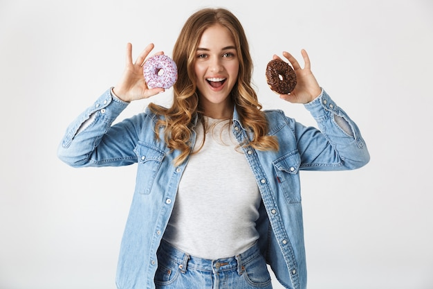 Attractive cheerful young girl standing isolated over white , holding tasty donuts