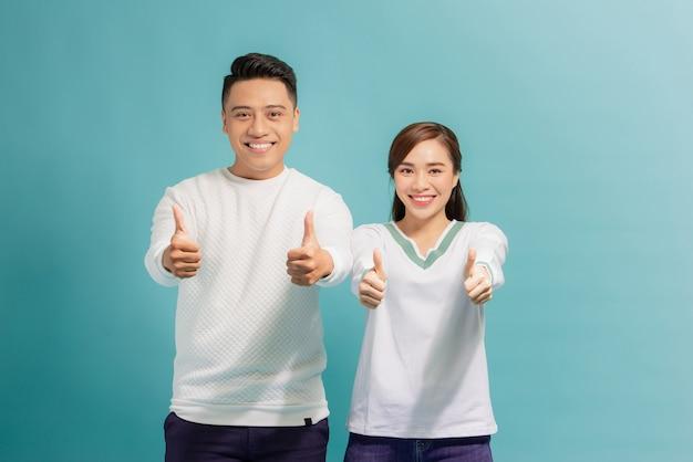 親指を立てる魅力的な陽気な若い恋人たち