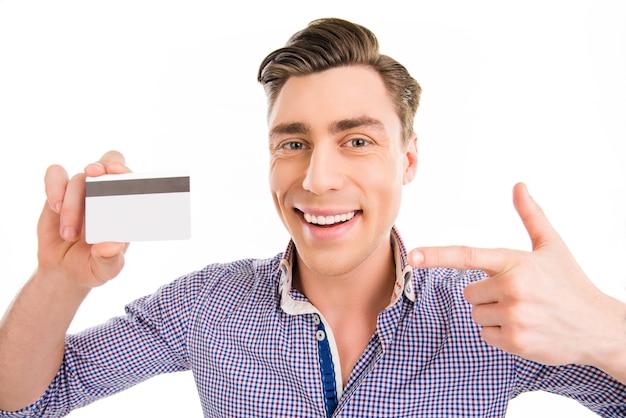 Привлекательный веселый молодой человек, указывая на банковскую карту