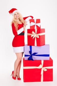 Привлекательная веселая молодая женщина в красном платье санта-клауса и шляпе позирует с подарочными коробками на белом фоне