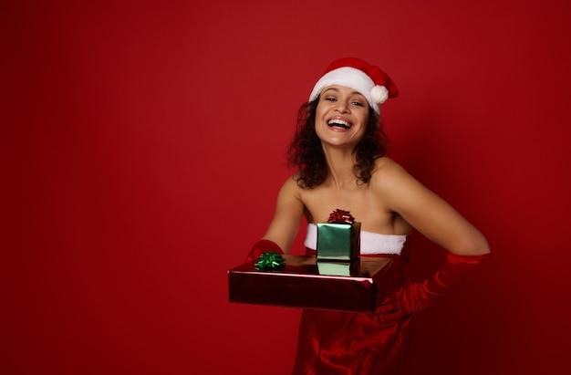 산타 카니발 의상을 입은 매력적인 쾌활한 젊은 여성이 반짝이는 빨강 및 녹색 포장 선물 종이로 싸인 아름다운 크리스마스 선물을 들고 포즈를 취하고 있으며, 광고 복사 공간이 있는 빨간색 배경 위에 격리되어 있습니다.