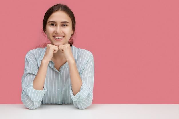 Impiegato di ufficio attraente giovane donna allegra con un ampio sorriso felice godendo la giornata lavorativa seduto alla scrivania bianca contro il muro rosa vuoto con copyspace per il contenuto pubblicitario