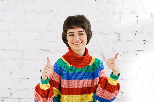 ストライプの短いセーターを着て承認を表明するために親指を上げる魅力的な陽気な若い女性...
