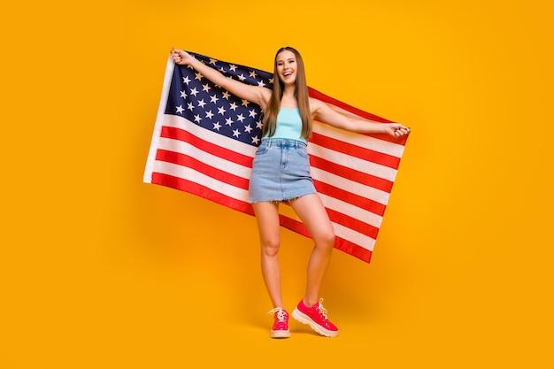 노란색 배경에 고립 된 큰 미국 국기를 들고 매력적인 쾌활 한 소녀