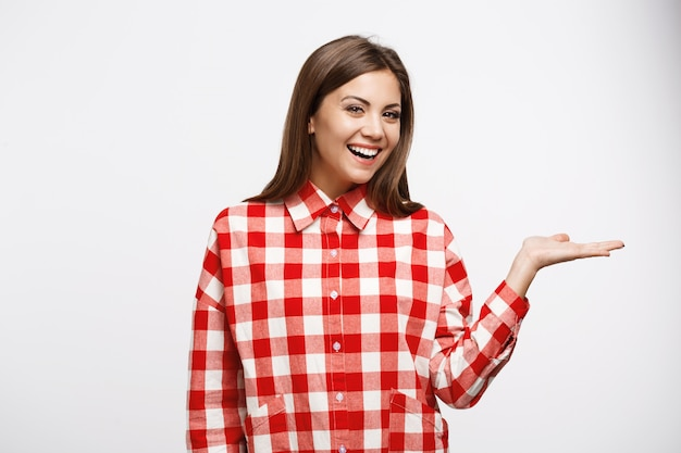 Attractive chestnut woman in red and white shirt looks straight