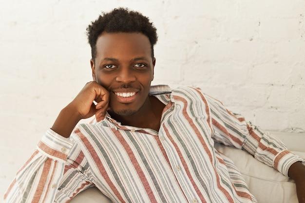 リビングルームのソファに快適に座って、あごに手を置いて、広い輝く笑顔でカメラを見て、ストライプのシャツを着た魅力的な陽気な若いアフリカ人男性