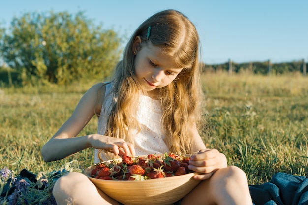 Attractive child girl eating strawberry in green meadow