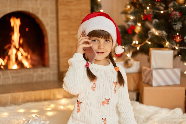 Attractive child wearing white pullover and santa claus hat talking phone in festive room