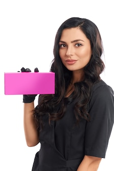 Attractive competent cosmetologist in medical uniform holding pink paper box