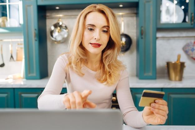 カードを持って、キッチンに座っている間彼女のラップトップで作業している魅力的な集中金髪の若い女性