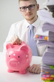 Привлекательный концентрированный человек, вставив монету в копилку в офисе, финансы
