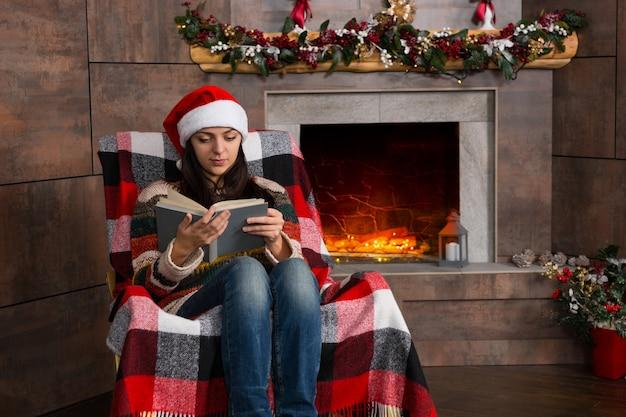 装飾された暖炉のあるリビングルームのクリスマスツリーの近くのロッキングチェアに座って面白いクリスマスの帽子を読んで魅力的な集中女性