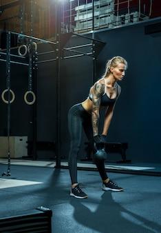スクワット姿勢でケトルベルで運動する魅力的な自信のある運動女性