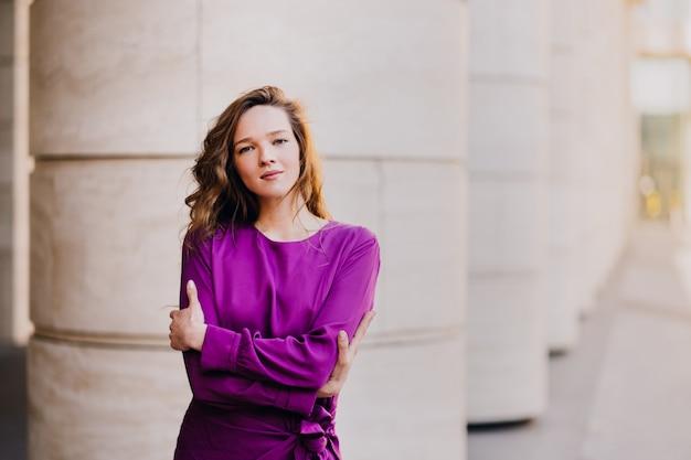 Привлекательная уверенно кавказская женщина в фиолетовом платье обнимает себя против размытого города