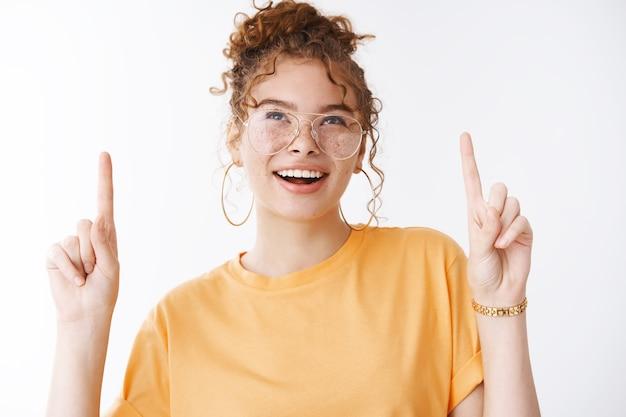 주황색 티셔츠를 입은 매력적인 자신감 넘치는 빨간 머리 주근깨가 매력적인 소녀는 인상적이고 호기심 많은 열린 입이 멋진 멋진 광고 프로모션을 가리키는 매혹적인 응시를 하고 있습니다.