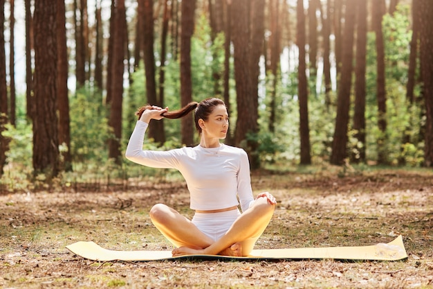 Attractive confident female wearing white top and leggins sitting on keremat on ground with crossed legs in lotus pose, looking thoughtfully aside, touching her ponytail.
