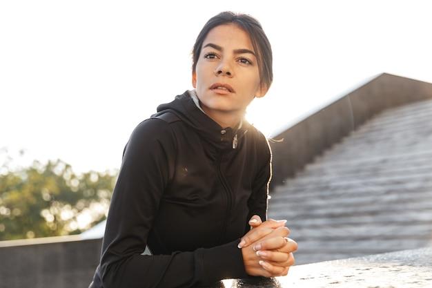 야외에서 운동하는 운동복을 입고 매력적인 자신감 피트 니스 여자 포즈