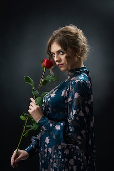 Attractive confident girl wearing blue fashionable dress with holding red rose.