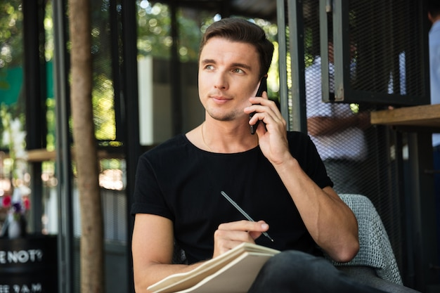 携帯電話で話している魅力的な自信を持って男性