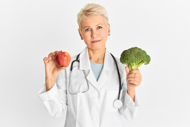 Attractive confident mature caucasian female doctor holding red apple and green broccoli as part of healthy diet to reduce risk of some chronic diseases. food, nutrition and health concept