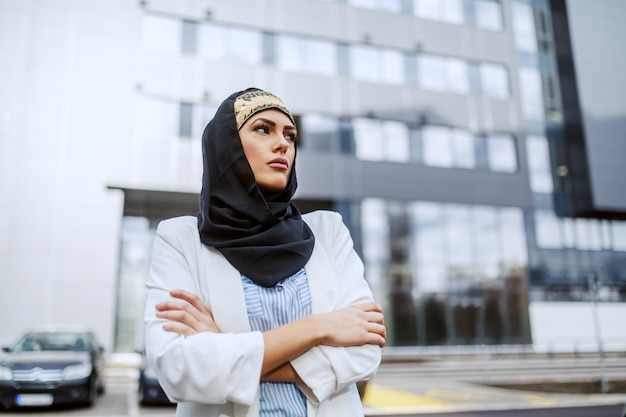 Attractive confident muslim businesswoman standing in front of her firm with arms folded.