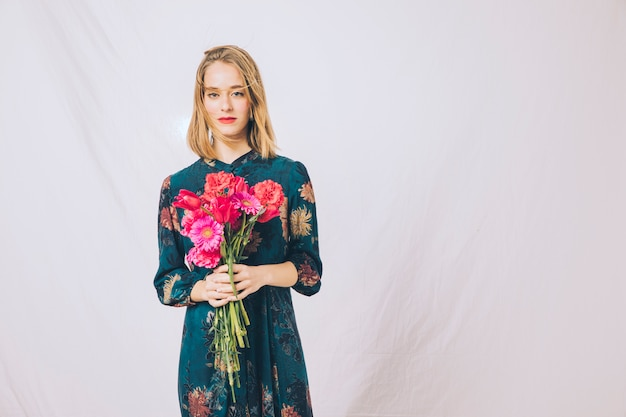 Attractive confident woman with bouquet of blooms