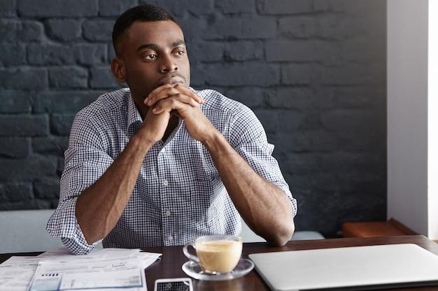Attraente giovane imprenditore maschio afroamericano fiducioso con sguardo premuroso e concentrato
