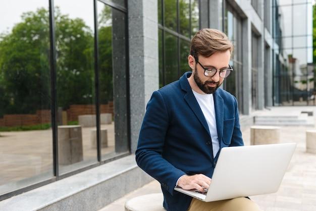 Привлекательный уверенно молодой бородатый мужчина в куртке работает на ноутбуке, сидя на улице в городе