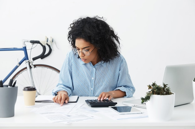 Attractive confident young businesswoman with curly hairstyle using calculator