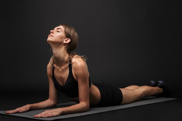 Привлекательная уверенно молодая здоровая фитнес-женщина в спортивном бюстгальтере и шортах, изолированных на черном фоне, упражнения на коврике для фитнеса, медитация
