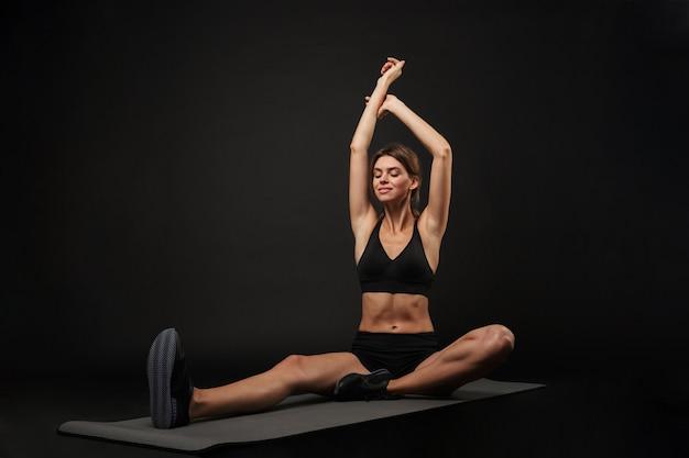 Привлекательная уверенно молодая здоровая фитнес-женщина в спортивном бюстгальтере и шортах, изолированных на черном фоне, упражнения на коврике для фитнеса, растяжка йоги
