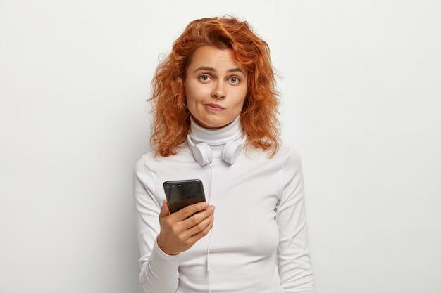 Attraente donna rossa confusa melomana ascolta musica tramite cuffie collegate allo smartphone, scarica canzoni su playlist, stringe le labbra, guarda confusa, indossa abiti bianchi. tecnologia, stile di vita