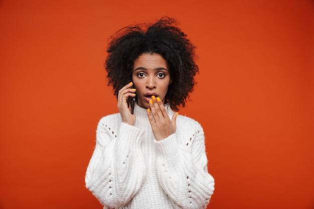 Привлекательная смущенная молодая африканская женщина в свитере разговаривает по мобильному телефону, изолированному над красной стеной