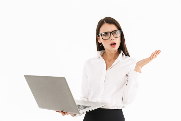 Attractive confused young businesswoman standing isolated over white wall, holding laptop computer
