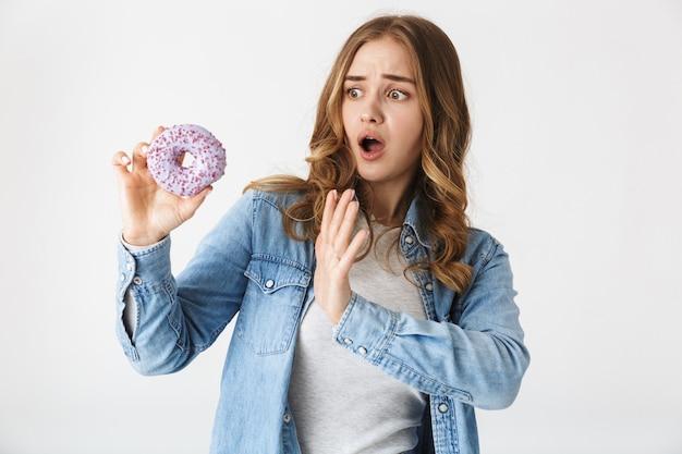 Привлекательная смущенная молодая девушка, стоящая изолированно над белой, держа вкусный пончик