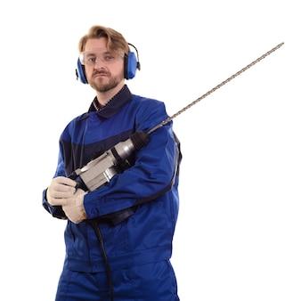 安全ゴーグルとヘッドホンを装着した魅力的な建設作業員がパンチャーを優しく握ります