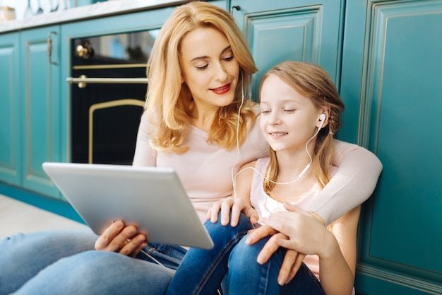Привлекательные довольные светловолосые мать и дочь улыбаются, сидят на полу на кухне, слушают музыку и обнимаются