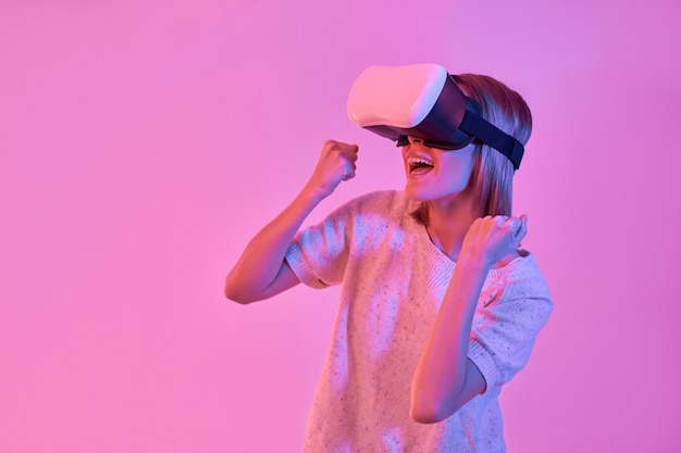 Attractive contented woman in casual wear using virtual reality glasses making victory gesture with hands isolated on neon pink