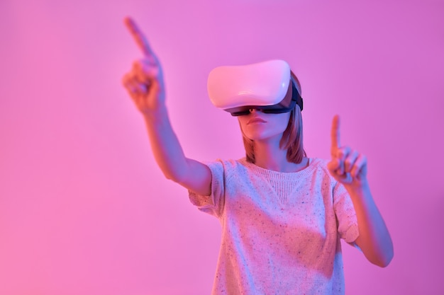 Attractive contented woman in casual wear using virtual reality glasses trying to press virtual buttons with her fingers isolated on neon pink