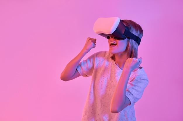 네온 핑크에 고립 된 손으로 승리 제스처를 만드는 가상 현실 안경을 사용하여 캐주얼웨어에 매력적인 만족 한 여자
