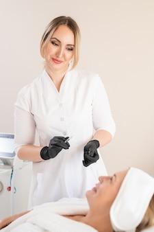 フィラーで満たされた注射器を保持し、クリニックでクライアントと話している手術用手袋の魅力的な美容師